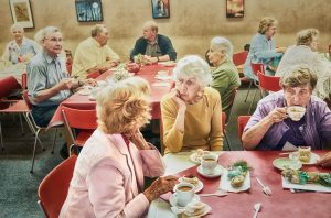 Photo of retirement home residents at a tea party. The interest of the photo is for the way 10 people pictured are relating to each other, attentively, longingly, indifferently, suspiciously...
